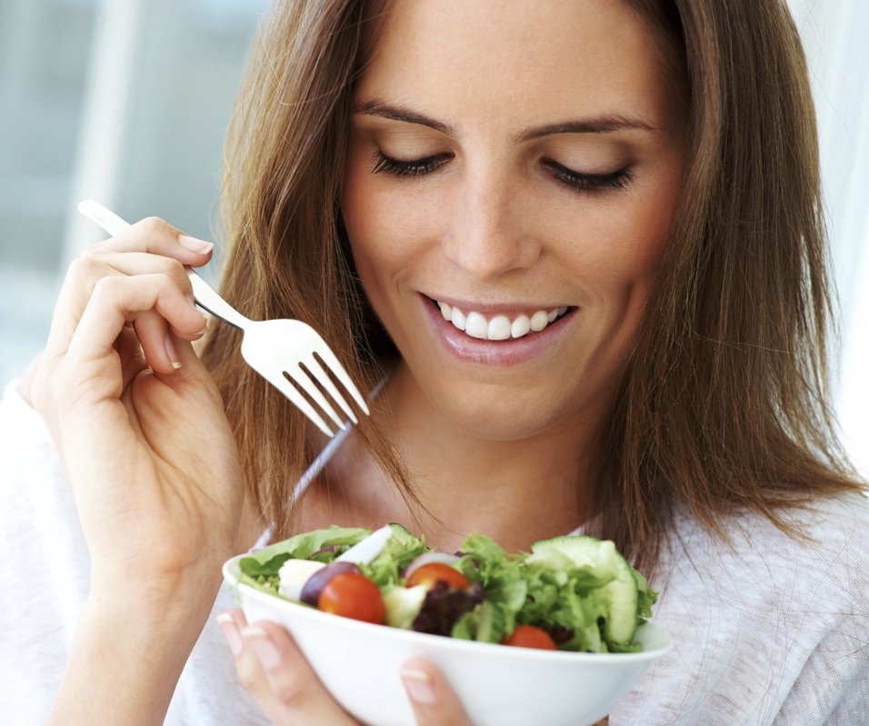 Close-up of young happy woman eating salad